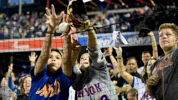 NEW YORK, NEW YORK - SEPTEMBER 27: Fans reach for a ball thrown by Robinson Cano #24 of the New York Mets during their game against the Atlanta Braves at Citi Field on September 27, 2019 in the Flushing neighborhood of the Queens borough of New York City.