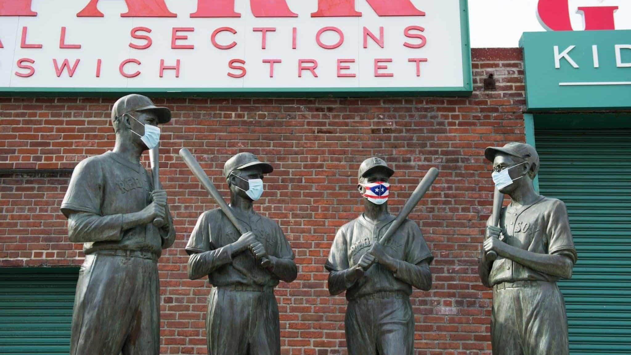BOSTON, MA - JULY 24: A mask is placed on the Teammates Statue on Ispwich Street on Opening Day at Fenway Park on July 24, 2020 in Boston, Massachusetts. The 2020 season had been postponed since March due to the COVID-19 pandemic. MLB