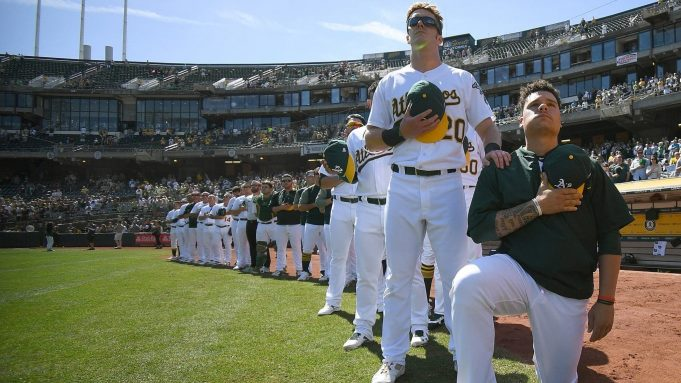 OAKLAND, CA - SEPTEMBER 24: Bruce Maxwell #13 of the Oakland Athletics kneels in protest next to teammate Mark Canha #20 duing the singing of the National Anthem prior to the start of the game against the Texas Rangers at Oakland Alameda Coliseum on September 24, 2017 in Oakland, California. New York Mets