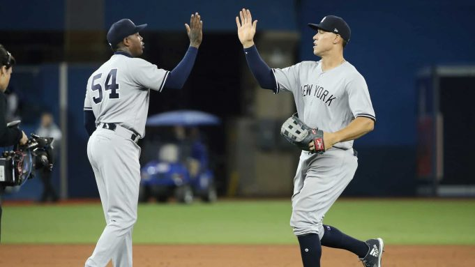 TORONTO, ON - MARCH 29: Aroldis Chapman #54 of the New York Yankees celebrates the victory with Aaron Judge #99 on Opening Day during MLB game action against the Toronto Blue Jays at Rogers Centre on March 29, 2018 in Toronto, Canada.
