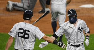 NEW YORK, NEW YORK - AUGUST 12: Clint Frazier #77 of the New York Yankees slaps gloved hands with DJ LeMahieu #26 after Frazier's home run in the second inning against the Atlanta Braves at Yankee Stadium on August 12, 2020 in the Bronx borough of New York City.