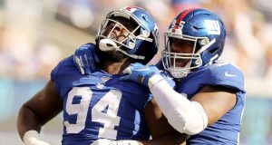 EAST RUTHERFORD, NEW JERSEY - SEPTEMBER 29: Dalvin Tomlinson #94 and B.J. Hill #95 of the New York Giants celebrate after they sacked Dwayne Haskins Jr. #7 of the Washington Redskins at MetLife Stadium on September 29, 2019 in East Rutherford, New Jersey.