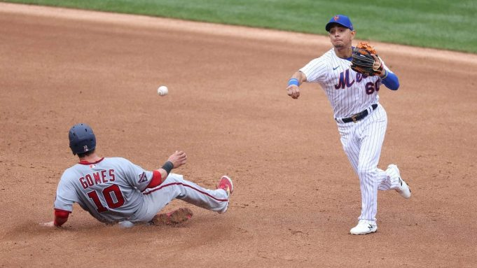NEW YORK, NEW YORK - AUGUST 13: Andres Gimenez #60 of the New York Mets attempts to turn a double play against Yan Gomes #10 of the Washington Nationals during their game at Citi Field on August 13, 2020 in New York City.