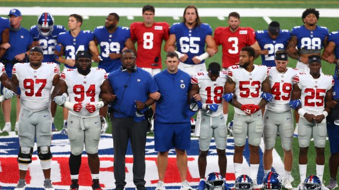 EAST RUTHERFORD, NEW JERSEY - AUGUST 28: New York Giants lock arms in a pregame moment of silence prior to the start of the Blue and White scrimmage at MetLife Stadium on August 28, 2020 in East Rutherford, New Jersey.