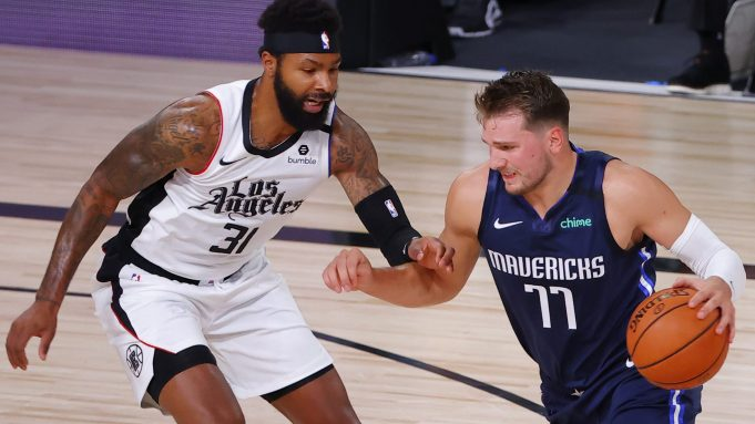 LAKE BUENA VISTA, FLORIDA - AUGUST 23: Luka Doncic #77 of the Dallas Mavericks drives against Marcus Morris Sr. #31 of the LA Clippers during the first quarter in Game Four of the Western Conference First Round during the 2020 NBA Playoffs at AdventHealth Arena at ESPN Wide World Of Sports Complex on August 23, 2020 in Lake Buena Vista, Florida. NOTE TO USER: User expressly acknowledges and agrees that, by downloading and or using this photograph, User is consenting to the terms and conditions of the Getty Images License Agreement.
