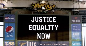 """MILWAUKEE, WISCONSIN - AUGUST 25: The scoreboard displays a message of """"Justice Equality Now"""" before the game between the Cincinnati Reds and Milwaukee Brewers at Miller Park on August 25, 2020 in Milwaukee, Wisconsin."""