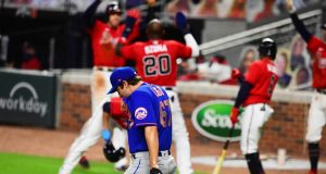 ATLANTA, GA - JULY 31: Seth Lugo #67 of the New York Mets heads back to the mound while members of the Atlanta Braves celebrate an eighth inning rally at SunTrust Field on June 31, 2020 in Atlanta, Georgia.