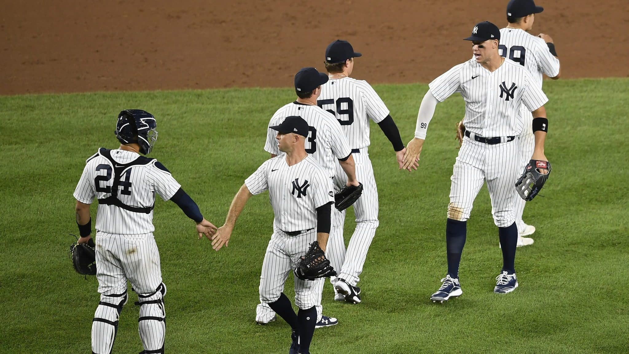 NEW YORK, NEW YORK - AUGUST 03: The New York Yankees high-five after winning 6-3 against the Philadelphia Phillies at Yankee Stadium on August 03, 2020 in the Bronx borough of New York City.