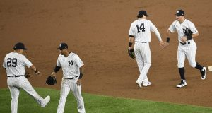 NEW YORK, NEW YORK - AUGUST 11: Gio Urshela #29, Aaron Hicks #31, Tyler Wade #14, and Mike Tauchman #39 of the New York Yankees celebrate after the ninth inning against the Atlanta Braves at Yankee Stadium on August 11, 2020 in the Bronx borough of New York City. The Yankees won 9-6.