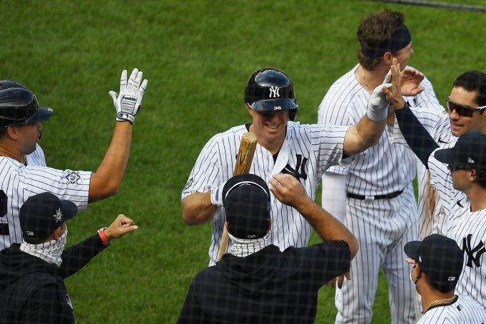 NEW YORK, NEW YORK - AUGUST 29: The New York Yankees high-five Erik Kratz #42 (C) after his at-bat where he attempted to bunt, allowing teammate Clint Frazier #42 (not pictured) to score on a wild pitch during the ninth inning against the New York Mets at Yankee Stadium on August 29, 2020 in the Bronx borough of New York City. The Yankees won 2-1. All players are wearing #42 in honor of Jackie Robinson Day. The day honoring Jackie Robinson, traditionally held on April 15, was rescheduled due to the COVID-19 pandemic.
