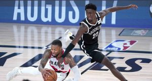 LAKE BUENA VISTA, FLORIDA - AUGUST 13: Damian Lillard #0 of the Portland Trail Blazers falls while chasing the ball against Caris LeVert #22 of the Brooklyn Nets in the second half at AdventHealth Arena at ESPN Wide World Of Sports Complex on August 13, 2020 in Lake Buena Vista, Florida.