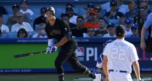 New York Yankees' Aaron Judge, left, runs to first as he hits a solo home run as Los Angeles Dodgers starting pitcher Clayton Kershaw watches during the third inning of a baseball game Sunday, Aug. 25, 2019, in Los Angeles.